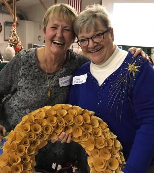 Two women smiling and holding a holiday wreath.