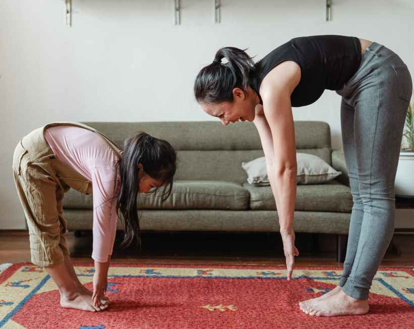excited barefoot ethnic mother and cute girl doing stretching exercises together yoga holistic healing kids