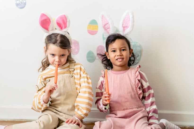 diverse little girls eating carrot while celebrating easter