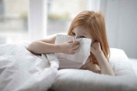 sick little girl blowing nose with tissue lying in bed