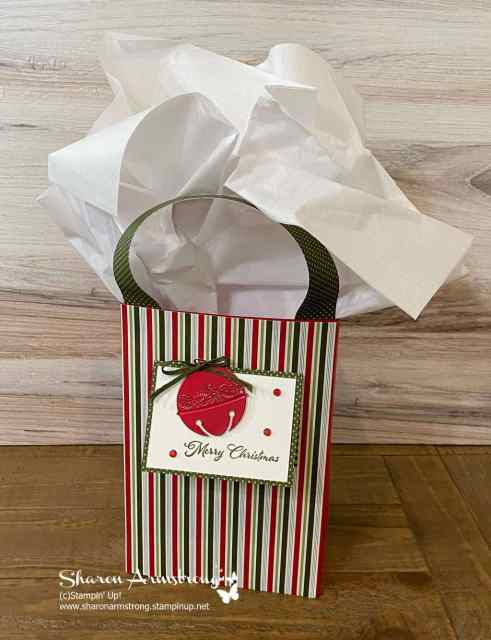 Grab some cardstock and a little scrapbook paper and you can DIY this gift bag quickly and top it with a die cut ornament.