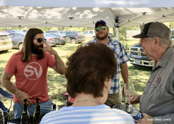 Ron Yates and Reagan Sivadon visiting with festival attendees at the Ron Yates Wine booth