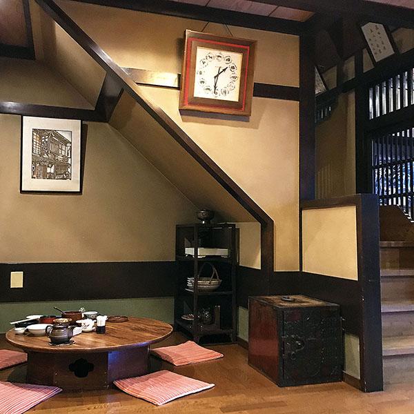 懐かしい風情の店内。個人的には卓袱台風の円卓がとても気に入っています。壁には京都在住の有名版画家が手掛けた「店の玄関」を描いた作品がかけられていました。