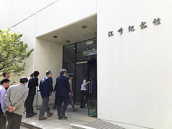 白い大きな江崎記念館。2階が企業ショールーム、1階が舞台付きの集会場になっています。