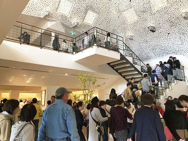 2階のカフェに続く入場待ちの行列。天井の黒い点は「備長炭」による装飾。