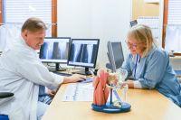 Lääkäri ja hoitaja istuvat pöydän ääressä katsomassa röntgenkuvia