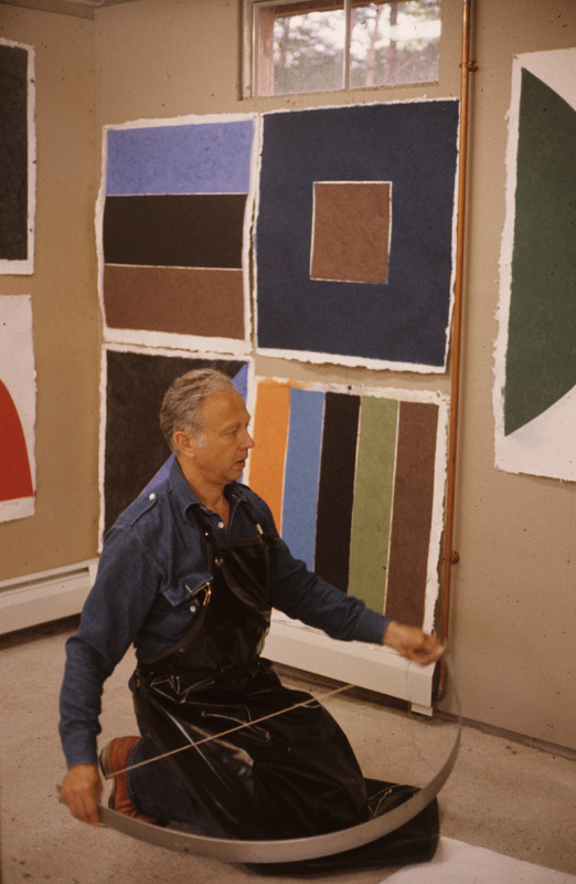 Ellsworth Kelly holding a semicircular mold for use in his 'Coloured paper image' series, Tyler Graphics Ltd., Bedford Village, New York, 1976. Photograph by Betty Fiske