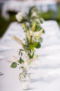 simple sophisticated wedding table, wedding tablescape, lilies, ferns, white and green flowers, tea light candles, outdoor beach wedding decor ideas