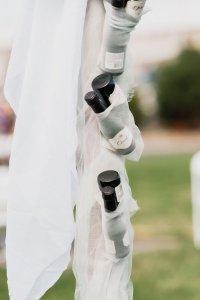 champagne hidden in wedding arch, navy green white wedding, wedding arch, champagne wedding, outdoor beach wedding