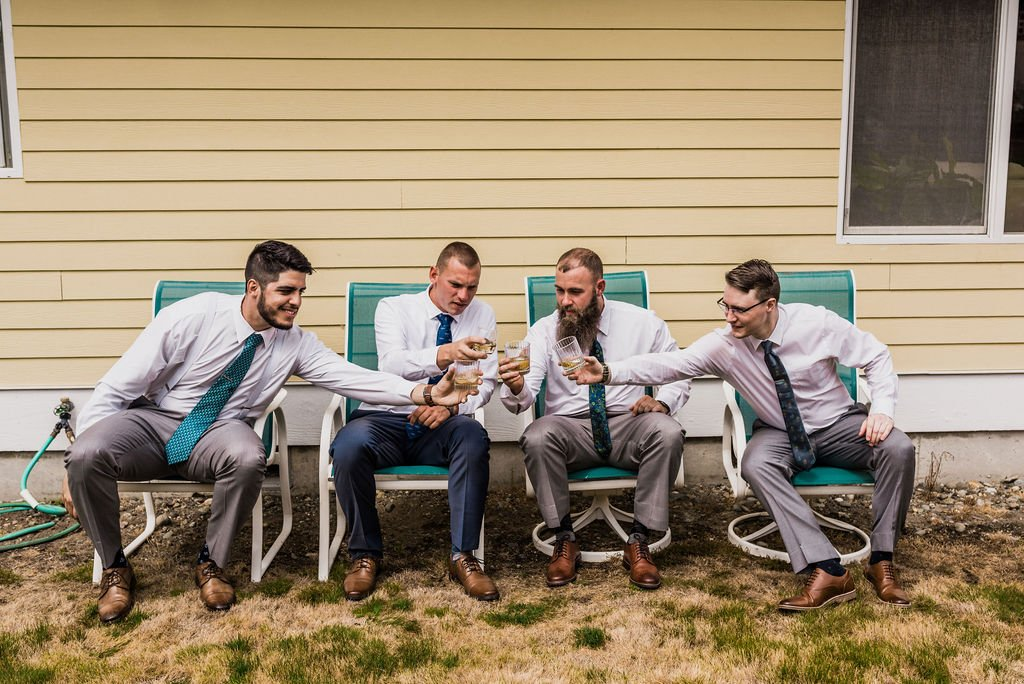 groomsmen and groom share a drink, cheers, lawmchairs