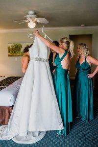 bride putting on wedding dress, emerald bridesmaids dresses