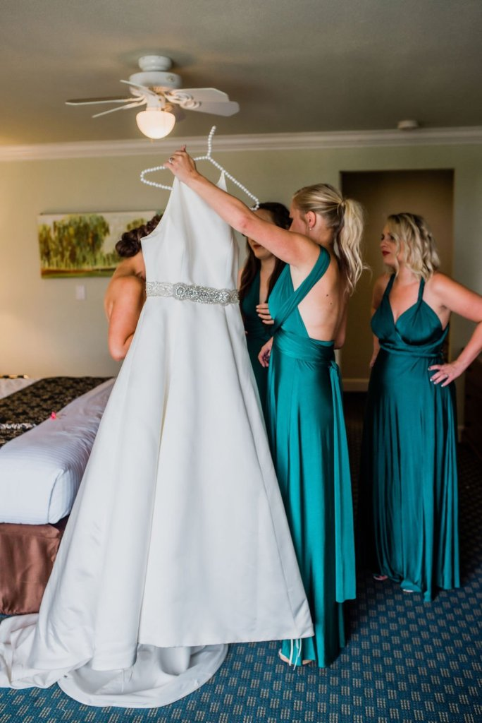 bride putting on wedding dress, emerald bridesmaids dresses