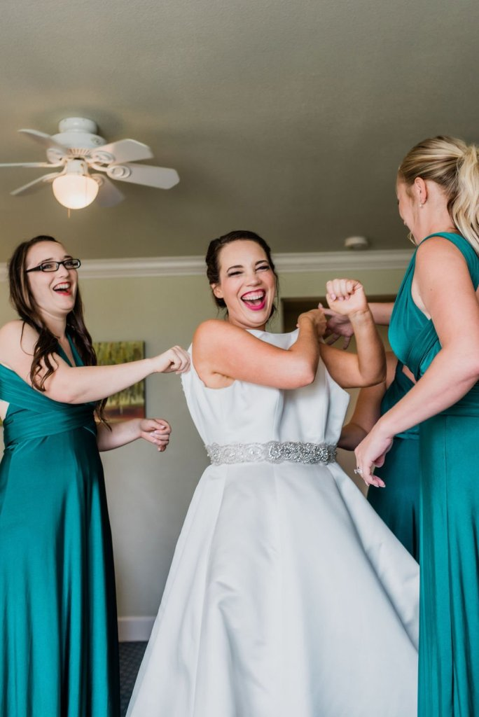 putting on wedding dress, bride and bridesmaids getting ready for wedding, bride laughing