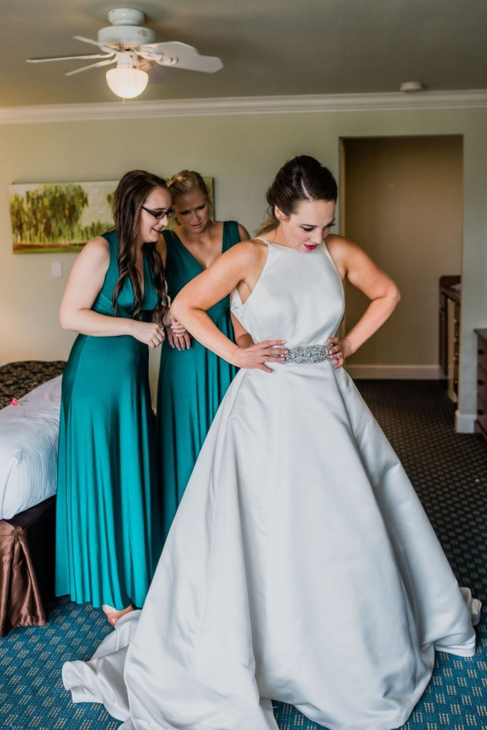 putting on wedding dress, bride and bridesmaids getting ready for wedding