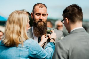 groomsmen putting on boutonnière at Pacific Northwest beach wedding gray suit