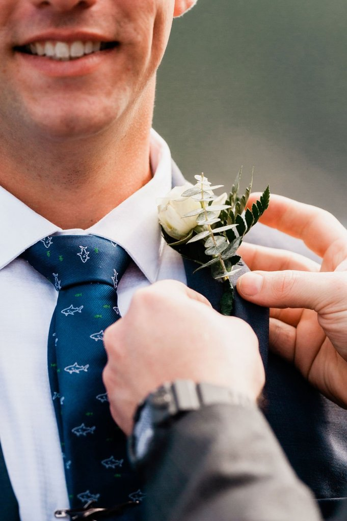 putting on groom's boutonnière, white and green wedding flowers, shark tie, dark gray suit