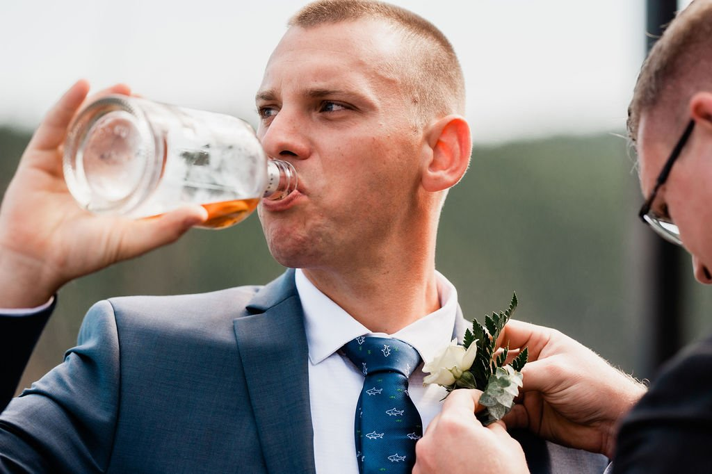 grooms swigs whiskey during wedding day preparations, shark tie, dark gray suit