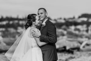 black and white wedding photography, bride and groom on beach, classic wedding dress, fingertip length veil, smiling groom