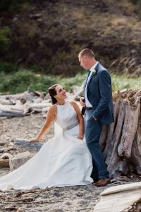 bride and groom on beach sitting on driftwood, Pacific Northwest wedding, destination wedding, dark gray suit