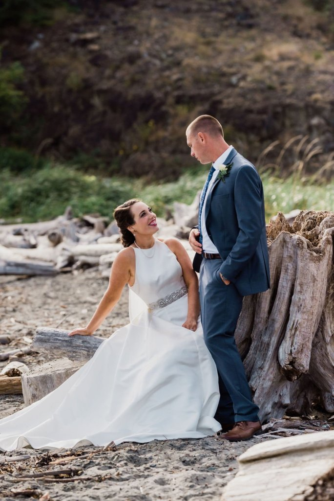 bride and groom on beach sitting on driftwood, Pacific Northwest wedding, destination wedding, dark gray suit