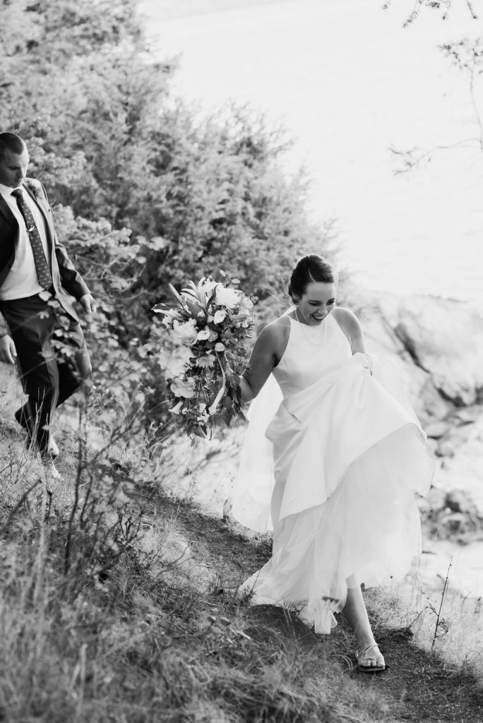 bride and groom walking along cliffside, adventure wedding photography