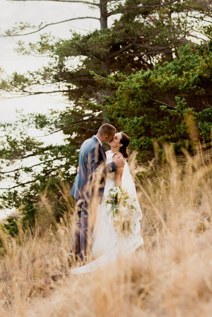 bride and groom kissing on mountain trail through grass