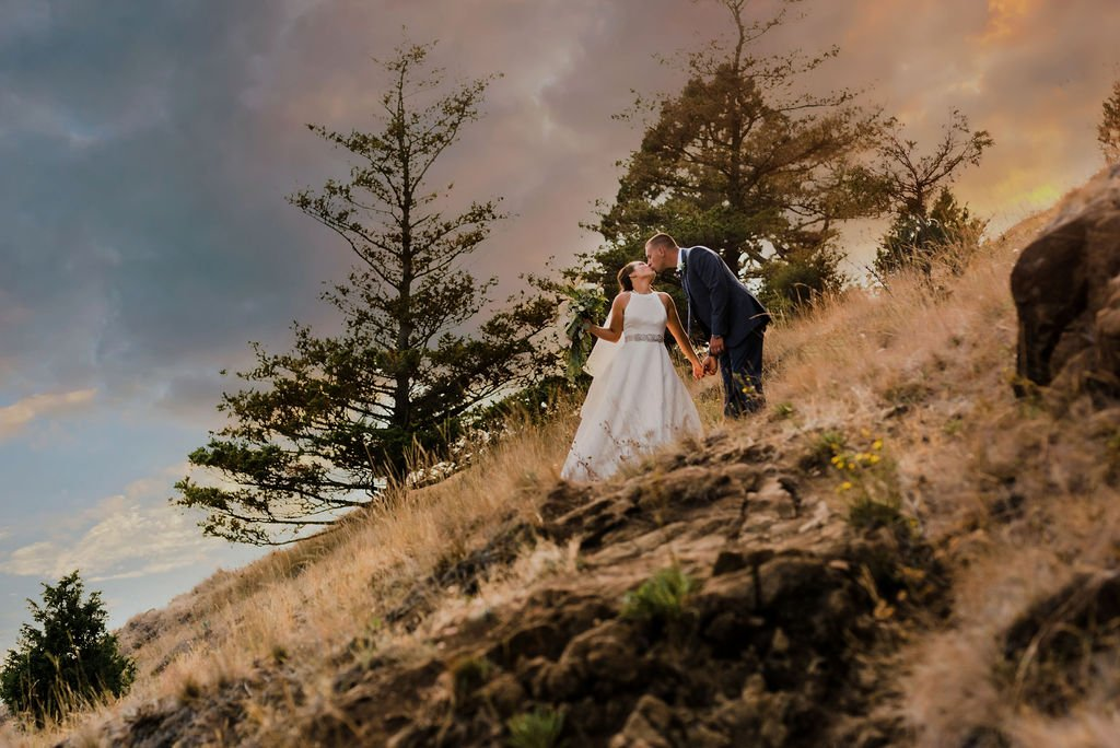bride and groom on mountain side with sunset, adventure wedding photography, Pacific Northwest wedding portraits
