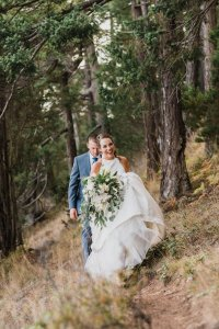Pacific Northwest adventure wedding photography, bride and groom on trail in woods with green and white flowers