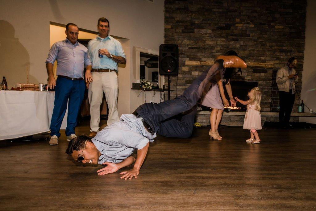 wedding guests breakdancing at wedding reception dance floor