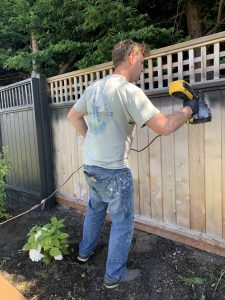 spraying cedar wood fence black with color stain