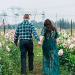 couple walking away in flower field of pink dahlias in Bellingham washingon