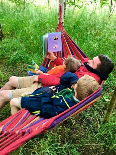 Dad and 2 children reading in hammocks at the Woodland Library at Timber Festival
