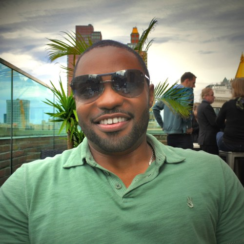 John Varvatos worn by musician producer celebrity Tyrone Smith in NYC Empire State Building with Louis Vuitton shades and La Prairie products