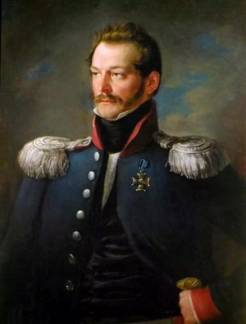 Zwrócony w lewą stronę mężczyzna w wieku ok. 35 lat, z wąsami i bokobrodami, ukazany od pasa w górę. Ubrany jest w granatowy mundur z białymi epoletami obszytymi frędzlami.