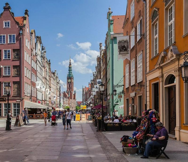 Widok na ulicę Długą w Gdańsku. Po obu stronach rząd kamieni, w oddali widoczny gotycki ratusz z wieżą.