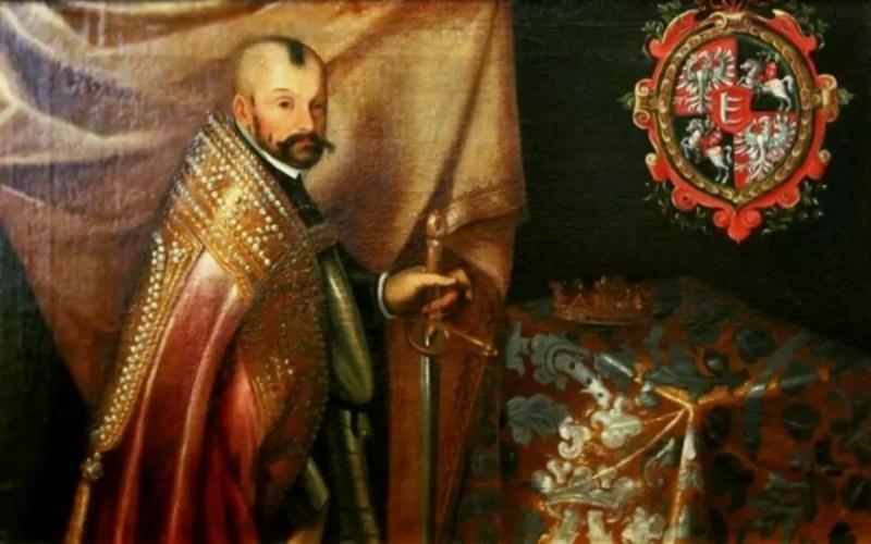 Mężczyzna w sumiastych wąsach klęczy w bogatym płaszczu przed stolikiem, na którym leży korona. W prawym górnym rogu kartusz heraldyczny ze skwadrowanym herbem Rzeczpospolitej Obojga Narodów z herbem Batorych na środku tarczy.
