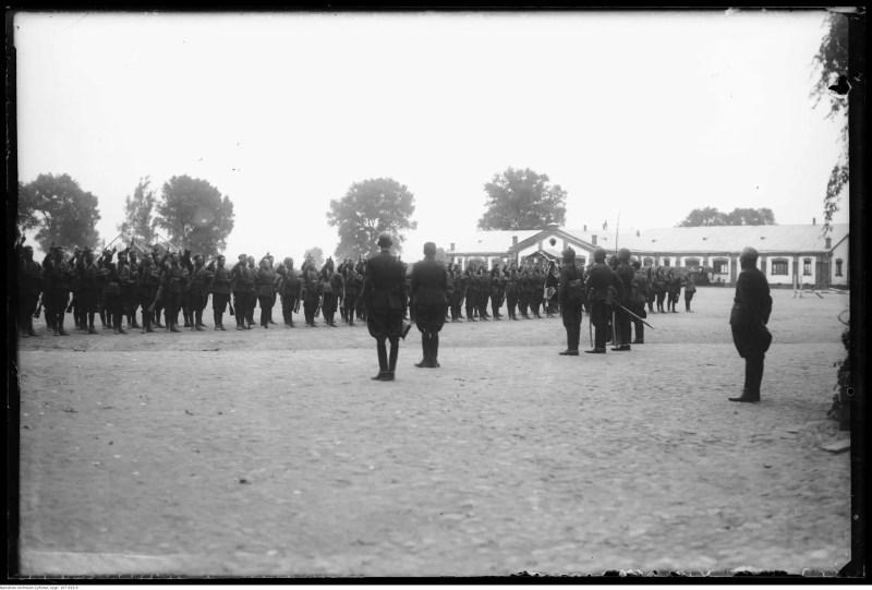 Na obszernym ziemnym placu żołnierze w dwuszeregu z prawymi rękoma uniesieonymi do przysięgi. Naprzeciw nich oficerowie oraz poczet sztandarowy.