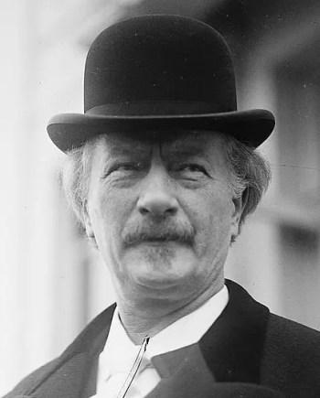 Portret starszego mężczyzny z wąsami, w meloniku, białej koszuli i czarnym płaszczu.