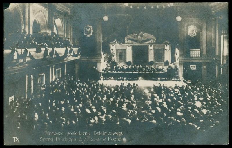 Tłum ludzi zebranych na widowni i galerii reprezentacyjnej sali teatralnej. Na scenie długi stół, za którym siedzą również uczestnicy sejmu. Za ich plecami na ścianie widoczne cztery herby Orzeł Biały.
