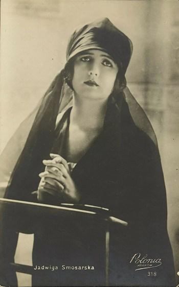 Jadwiga Smosarska w stoju żałobnym przy klęczniku, z rękoma złożonymi do modlitwy.