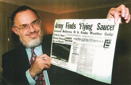 """Stanton Friedman mostrando la portada del periódico """"Los Angeles Herald Express"""" de 1947 en donde se puede apreciar un titular bastante interesante que indica el comienzo de una campaña de encubrimiento del tema OVNI por parte del gobierno de EE.UU."""