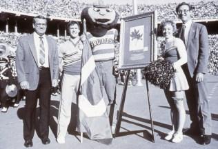 Group photo of Daniel Crawford, Brutus, Tod Stuessy, the original buckeye, and OSU cheerleaders in the stadium during the OSU—Iowa football game.