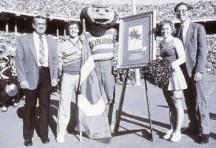 Group photo of Daniel Crawford, Brutus, Tod Stuessy, the original buckeye, and OSU cheerleaders in the stadium during the OSU—Iowa football game.