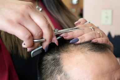 Galloso cuts a clients hair.