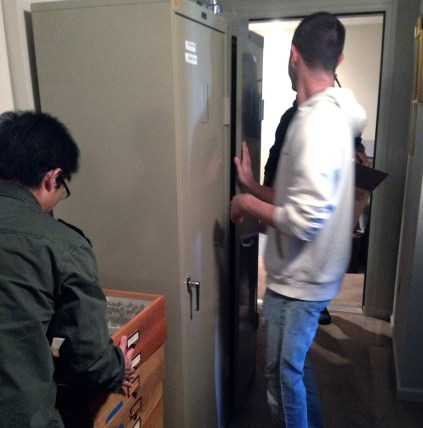 Matt (standing) and Huayan (with the drawers) remove all the drawers from a metal cabinet in order to move it down the stairs.