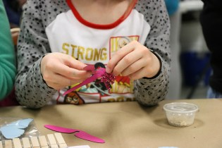 A child puts together a dragonfly with pipe cleaner legs.