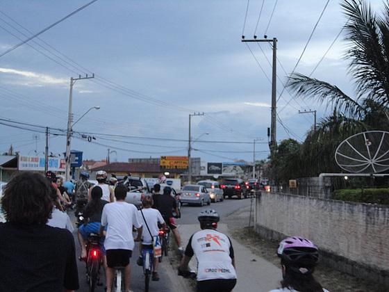 Com acostamento intermitente, ciclistas aguardam atrás dos automóveis a sua vez de se deslocar.