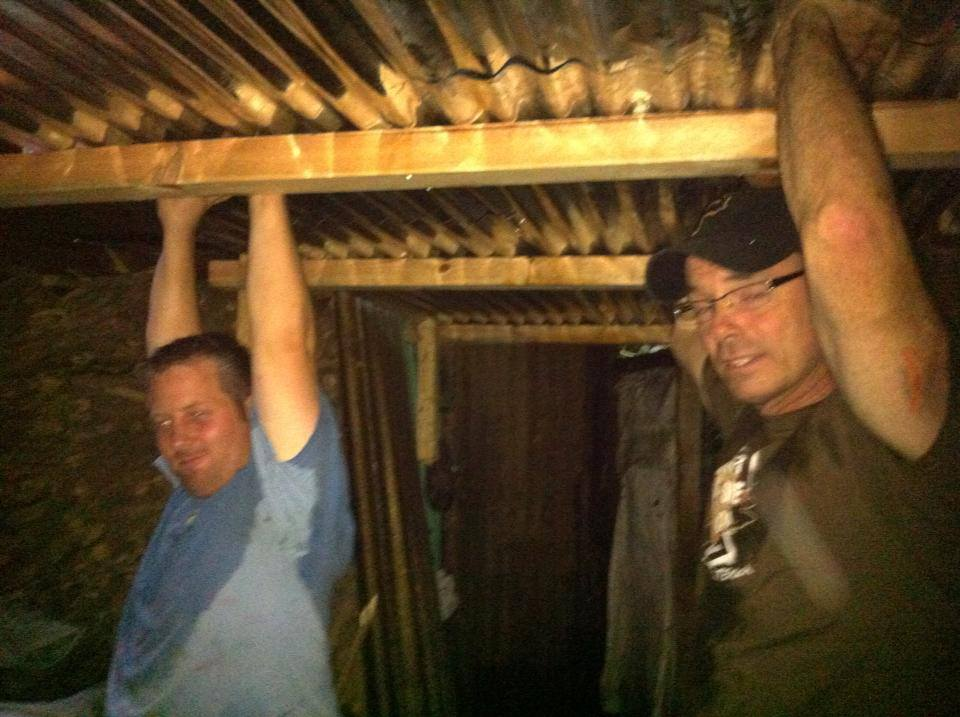 Two guys in July holding up the roof while the Guatemalans nail it down in the rain.