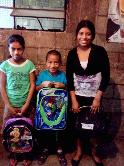 (right to left) Dincy, Jairo, and Yanira receiving school supplies through Servants last year.
