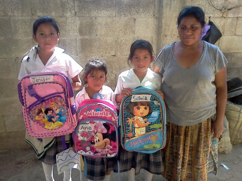 Apolonia's girls receiving backpacks and school supplies for school last year.